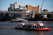 Scene of the River Thames, London. Running through the heart of the city. Tourist boats / cruises pass Millennium Bridge