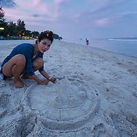 Pare building sand stupas on the beach in Hua Hin.