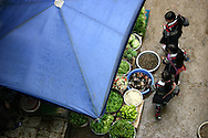 Three young women from the Black Hmoung minority group check out the food offerings as they make their way through the large outdoor market in Sapa. Robert Dodge, a Washington DC photographer and writer, has been working on his Vietnam 40 Years Later project since 2005. The project has taken him throughout Vietnam, including Hanoi, Ho Chi Minh City (Saigon), Nha Trang, Mue Nie, Phan Thiet, the Mekong, Sapa, Ninh Binh and the Perfume Pagoda. His images capture scenes and people from women in conical hats planting rice along the Red River in the north to men and women working in the floating markets on the Mekong River and its tributaries. Robert's project also captures the traditions of ancient Asia in the rural markets, Buddhist Monasteries and the celebrations around Tet, the Lunar New Year. Also to be found are images of the emerging modern Vietnam, such as young people eating and drinking and embracing the fashions and music of the West. His book. Vietnam 40 Years Later, was published March 2014 by Damiani Editore of Italy.