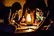 CHOWKIPUR, INDIA, - SEPTEMBER 18: Boys study by lantern light in a house L-R: (children closest to camera) Nitish Suraj (12), Ashish Choudhary (10), Baijunath Paswan (7) in Chowkipur India on September 18, 2015. Chowkipur is a village 60 KM from Patna that has no electricity. (Photo by Simon de Trey-White )