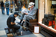 A man has his shoes shined whilst he reads a newspaper in the Burlington Arcade an expensive shopping arcade between Piccadilly and Bond Street London, UK