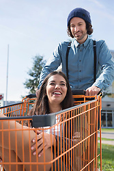 Young man couple fun pushing shopping trolley