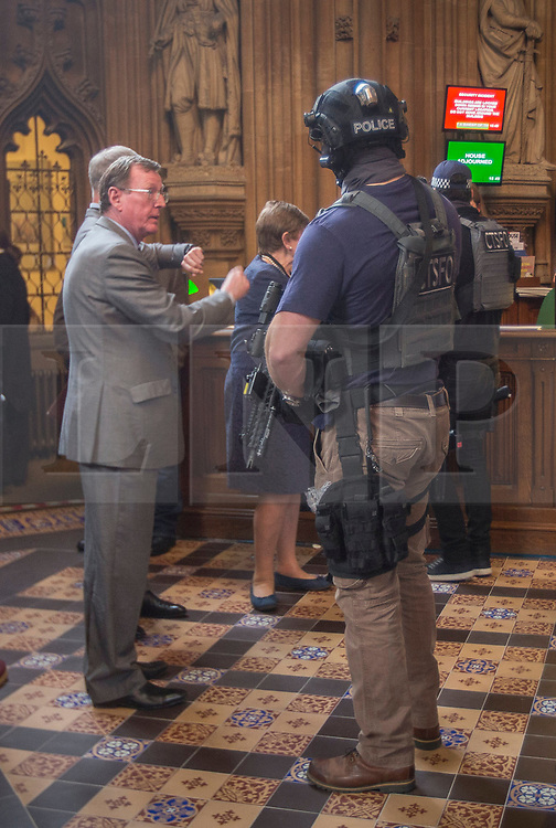 © Licensed to London News Pictures.22/03/2017. London, UK. Former Northern Ireland First Minister David Trimble stands near an armed policeman in the Central Lobby  during a lockdown in Parliament after a terrorist attack in Westminster.Photo credit: Alison Baskerville/LNP<br /> <br /> <br /> MP's and members of the public are held in Central Lobby in the Houses of Parliament as the building is locked down following a suspected terror attack.