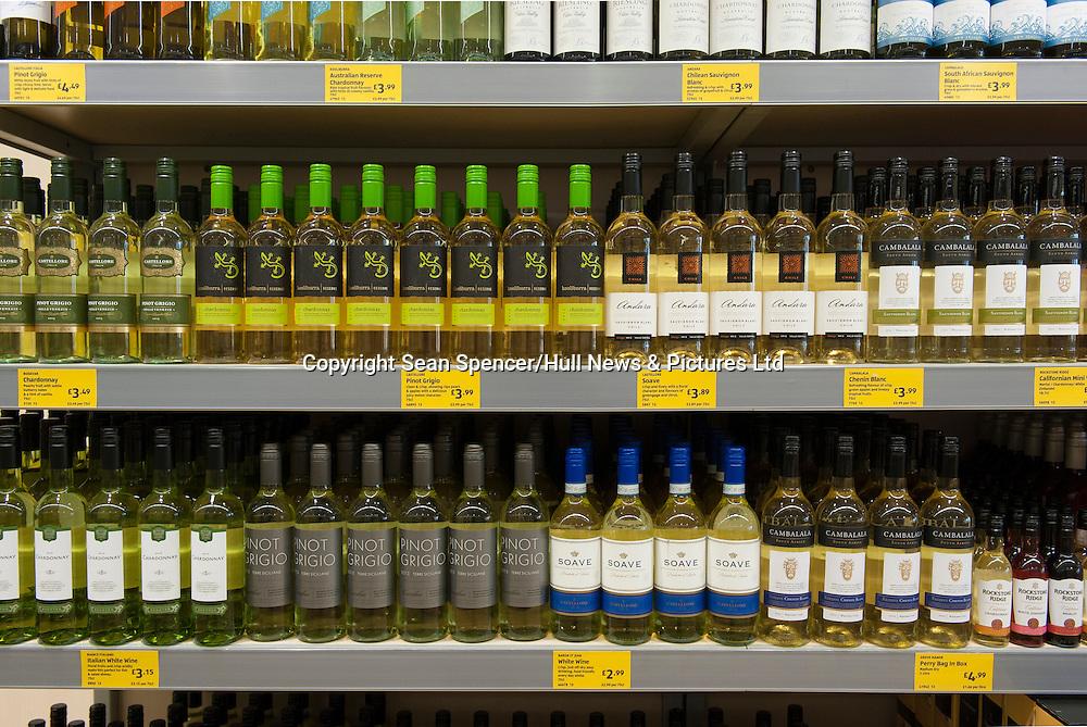 Bottles of cheap white wine on shelves in a UK budget supermarket.