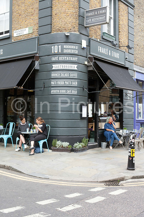 People eating al fresco outside a bar in Shoreditch, London, UK<br /> Shoreditch, an area that was dominated by light industry is now home to cafes and fashionable restaurants and cafes