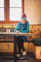 A woman reads a magazine while staying at the Opus Hut, San Juan Range, Colorado.