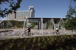 Stock photo of cyclists riding through the park by the fountains