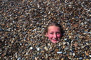 Young girl's face nearly covered by pebbles on a shingle beach