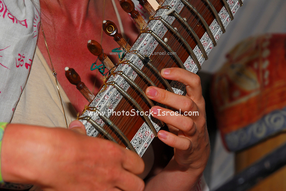 Close up of the hands of a man playing a sitar