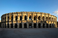 Arena at Nimes - In the cities of the Roman Empire, the arena was the venue of choice for epic shows such as gladiator events.  These amphitheaters were also symbols of a city's prestige. The arena at Nimes is one of the best preserved from the Roman past. The arena's shape is elliptical with sixty arches that cover the two levels.  Inside there are 34 rows of seats that can accommodate 20,000 spectators. Beneath the seating, concentric galleries lead to different levels by way of more than 100 staircases.  It had been believed that Augustus bestowed the amphitheatre on the city but it is now agreed that its construction dates from the 1st century - around the same time as the Colosseum of Rome.  Following the fall of the Roman Empire, the arena was became a fortified village with wells, houses and even churches up until 1786 when the buildings were removed and restoration of the arena began. In 1813 Nimes started to hold the first bullfights at the arena. Although somewhat controversial,  the bullfights and other events are what has enabled the full restoration and preservation of the Arena of Nimes.