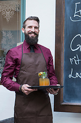 Smiling young man holding mocktail on tray