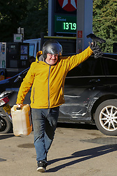 © Licensed to London News Pictures. 29/09/2021. London, UK. A man with a large container full of motor fuel at Texaco petrol station in north London on the sixth day of the fuel crisis, amid fears of fuel running out due to a shortage of HGV drivers. According to the government, 75 army tanker drivers have been put on standby to deliver motor fuel in order to ease the chaos at petrol stations. Photo credit: Dinendra Haria/LNP