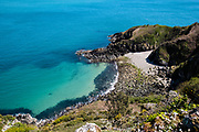 Vicard harbour, a tiny pebbly cove hidden in the headland on the north coast of Jersey CI, looking clam and pristine on a Spring day with clear turquoise water lapping the shoreline.