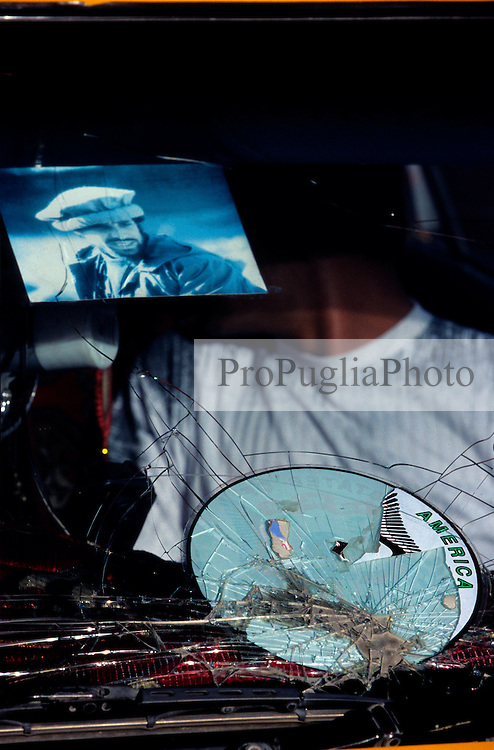 KABUL, 17 JULY 2005..A smashed car window displaying the picture of  Gen Ahmad Shah Massoud , known as the Lion of Panjshir for his success in fighting the Soviet, and the remainings of USA sticker. .In Afghanistan most of the car window are broken due to bad road conditions.