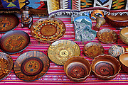 "Carved and decorated wood Andean plates are sold at Aguas Calientes village (""Machupicchu Town"") at the foot of Machu Picchu, in Peru, South America."