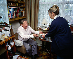 Meals on wheels delivery to elderly man living at home, London UK
