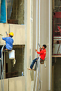 16 OCTOBER 2012 - BANGKOK, THAILAND: Workers swinging on ropes caulk seams in an exterior concrete wall at a residential condominium project on Th Phaya Thai near the intersection with Phetchaburi Rd. in Bangkok. The global economic slowdown had little visible effect in Bangkok. Construction projects dot the city of 12 million and development continues unabated.    PHOTO BY JACK KURTZ