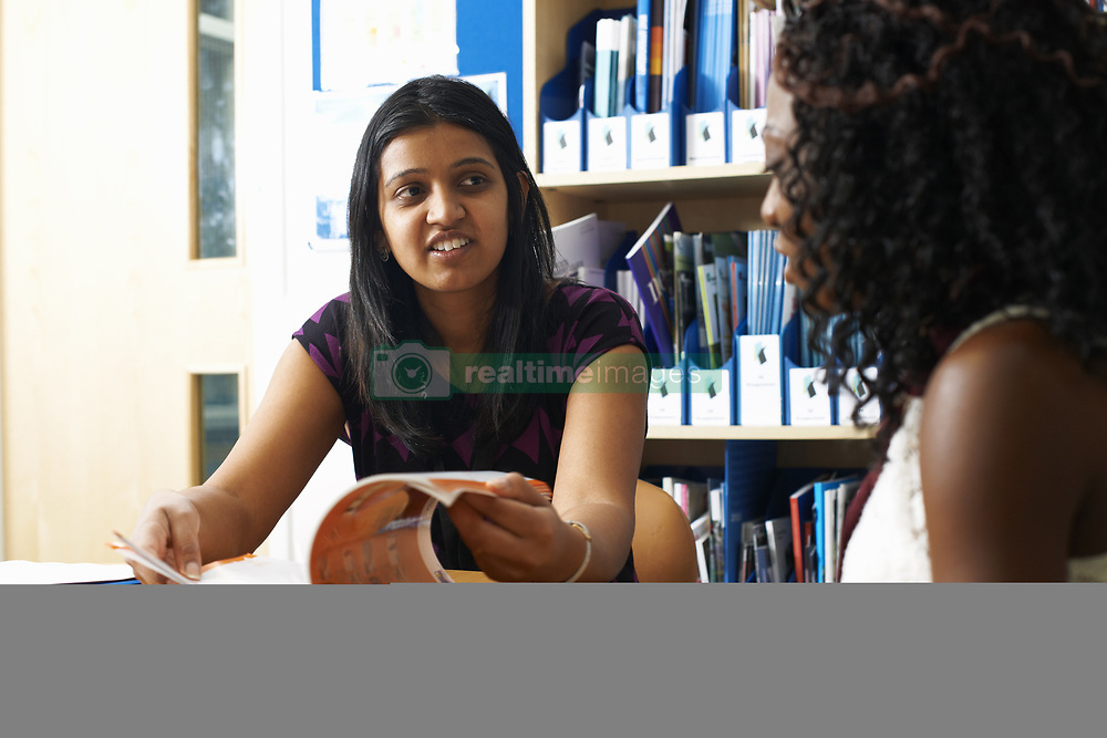 June 25, 2014 - Female lecturer having tutorial with female student in college classroom (Credit Image: © Image Source/Image Source/ZUMAPRESS.com)