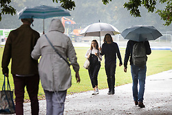 © Licensed to London News Pictures. 19/09/2021. London, UK. Members of the public shelter under umbrellas during a rain shower in Greenwich Park, South East London. A yellow weather warning for rain is in place for parts of England.  Photo credit: George Cracknell Wright/LNP