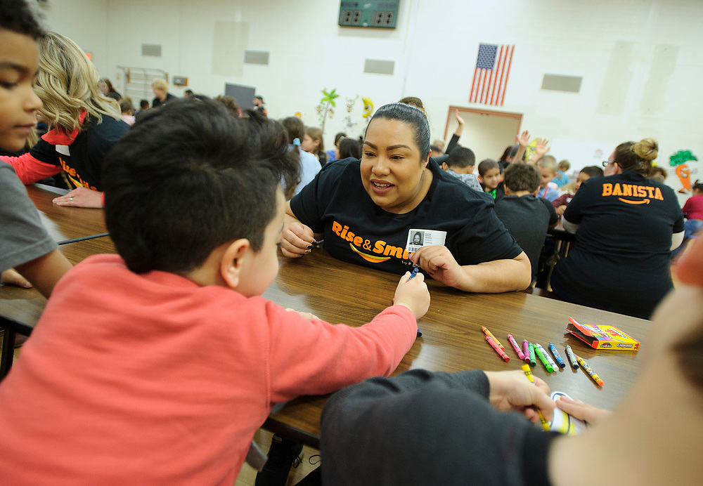 Amazon associate Noemi Veras interacts with children as over one hundred students participate in Amazon's Rise & Smile campaign breakfast event Nov. 9, 2018, at McAdoo Kelayres Elementary/Middle School in Hazleton, Pennsylvania. Amazon has partnered with Share Our Strength's No Kid Hungry campaign to help bring healthy breakfast to students across the country. (Photo by Matt Smith)
