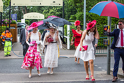Ascot, UK. 20 June, 2019. Racegoers shelter from the rain on Ladies Day at Royal Ascot.
