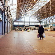 Elderly woman carrying grocery bags  at empty pavillion of RIbeira market