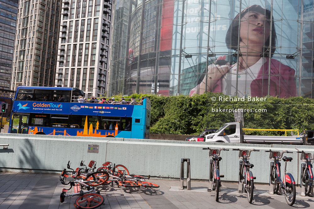 With a pile of collapsed Mobikes lying on the ground, a tour bus passes a large image of a woman appearing in an ad appears on the circular structure of the IMAX cinema at Waterloo, on 15th August 2019, in London, England.