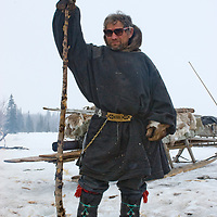 North of the Arctic Circle in Russia, nomadic Komi reindeer herder Stass Pan'kov rests on a stick as he waits for the reindeer herd to arrive to pull his sleds.