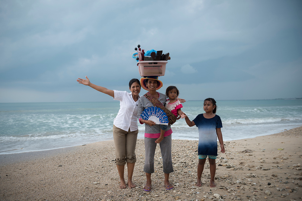 Bali, Indonesia - March 23, 2017: Metri, who works at the Intercontinental Bali Resort in Jimbaran, stands on the beach outside the hotel and poses with a woman and her children selling items on the beach.