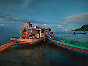 A family cooking diner of coral fish, over a fire. Bajau family living all year round on a Lepa, a traditional houseboat.