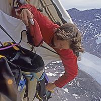 MOUNTAINEERING. Alex Lowe in portaledge camp high on overhanging granite wall on Great Sail Peak, Baffin Island, Nunavut, Canada.