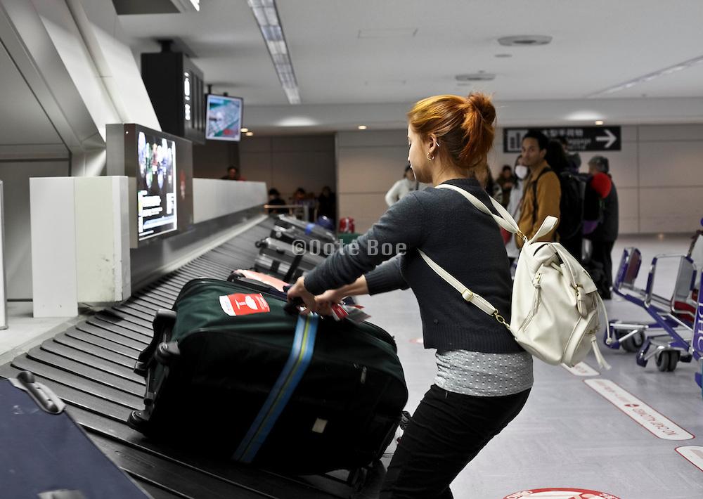 passengers getting her luggage at Narita airport Tokyo Japan