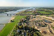 Nederland, Gelderland, Nijmegen, 24-10-2013; rivier de Waal met de spoorbrug met fietspad (De Snelbinder) , gezien vanuit het Oosten, daarachter de nieuwe stadsbrug van Nijmegen De Oversteek. Rechts van de rivier grondwerkzaamheden voor de dijkteruglegging Lent (Ruimte voor de Rivier). De dijken worden landinwaarts verplaats en er wordt een nevengeul gegraven. De huizen op de dijk blijven bestaan en komen te liggen op het Stadseiland Veur-Lent Nijmegen. In de verte de rookpluimen van de energiecentrale Electrabel Nederland.<br /> First bridge on the river Waal is the railway bridge with cycle path De Snelbinder (The Luggage strap) , next  and finally the new city bridge of Nijmegen De Oversteek (The Crossing). Right of the river groundwork for the Dike relocation of Lent (project Ruimte voor de Rivier: Room for the River). <br /> luchtfoto (toeslag op standaard tarieven);<br /> aerial photo (additional fee required);<br /> copyright foto/photo Siebe Swart.