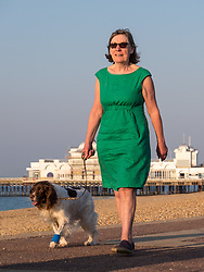 © Licensed to London News Pictures. 14/09/2016. Portsmouth, UK.  A woman walking her dog along Southsea promenade in the warm weather this morning, 14th September 2016. Temperatures are set to remain warm over the coming days in the south of England. Photo credit: Rob Arnold/LNP