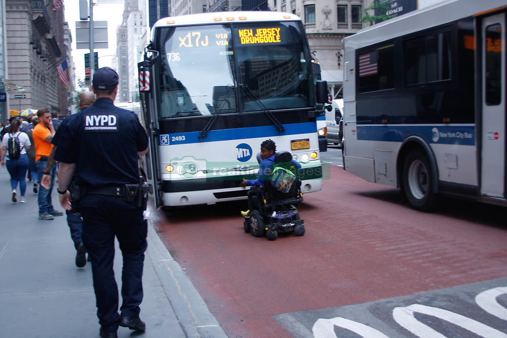 June 13, 2018 - New York, United States - A woman on a wheel chair with her child stood in front of a bus who refuses to allow her get inside on 5th Avenue New York,a block from Trump Tower. Police were called for and they finally convinced her to leave the road. She however got on another bus. (Credit Image: © Niyi Fote/Pacific Press via ZUMA Wire)