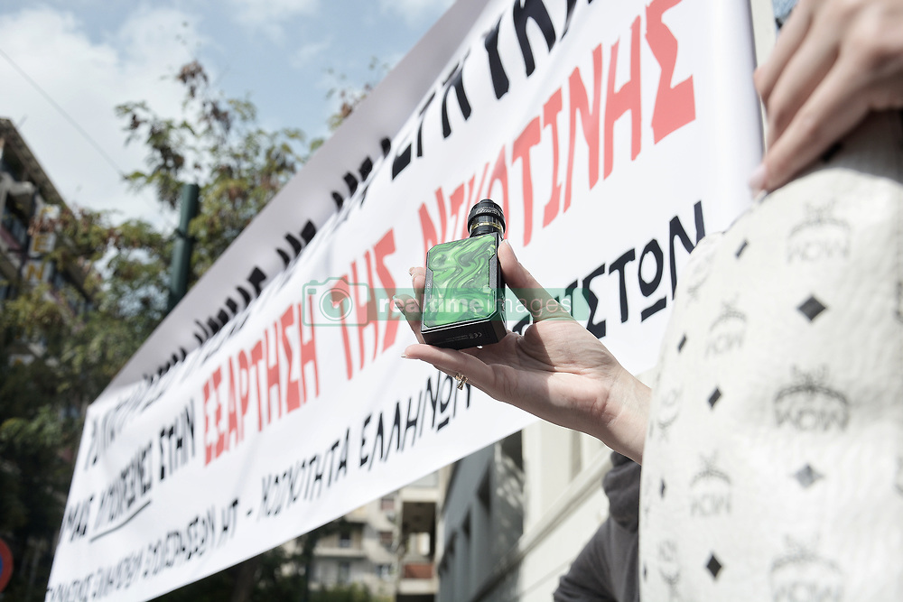 October 4, 2018 - Athens, Greece - A protester seen standing next to a banner holding a vapor cigarette during the protest..People protest outside the Ministry of Health, against the circular of Ministry of Health that bans the sale of vapor cigarettes (Credit Image: © Giorgos Zachos/SOPA Images via ZUMA Wire)