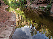 Warm summer morning light striking sandstone canyon walls is beautifully reflected in the still waters of West Fork, Oak Creek.