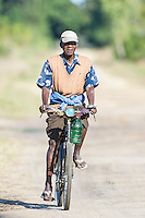 Mozambican riding his bicycle on a sandy track, Rio Savanne, Beira, Sofala Province, Mozambique