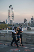 A female climate change activist looses a sandal as two male police officers carry her along Waterloo Bridge as the Extinction Rebellion protests enter their seventh day on the 21st April 2019 in London in the United Kingdom. The environmental campaign group has blocked a number of key junctions in central London in a bid to highlight the ongoing ecological crisis.