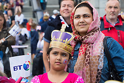 Trafalgar Square, London, June 12th 2016. Rain greets Londoners and visitors to the capital's Trafalgar Square as the Mayor hosts a Patron's Lunch in celebration of The Queen's 90th birthday. PICTURED: A girl and a woman watch the events taking place in the Mall on a big screen.