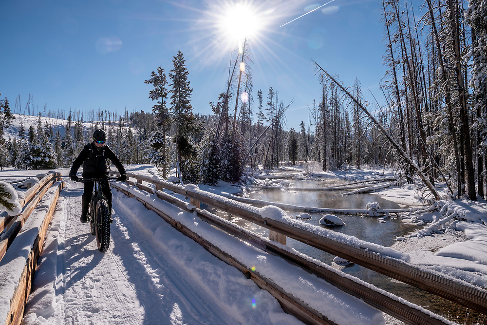 Snow biking across the Redfish Lake Outlet Bridge in mid winter with river and sun.  Licensing and Open Edition Prints.