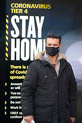 © Licensed to London News Pictures 07/01/2021.         Bexleyheath, UK. A man wearing a protective mask next to a stay home sign in Bexleyheath, South East London. A third national Coronavirus lockdown is in place in England. An estimated one in 30 people in London were infected with Covid-19 between December 27th and January the 2nd. Photo credit:Grant Falvey/LNP