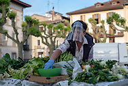 A farmer, wearing protective face screen, places the vegetables in her outdoor market stall. Irun (Basque Country). May 09, 2020. As the downscaling progresses, there are more and more businesses and commercial activities that take over their activity, after having been closed due to the blockade ordered by the Spanish government to prevent the spread of the COVID-19. (Gari Garaialde / Bostok Photo)