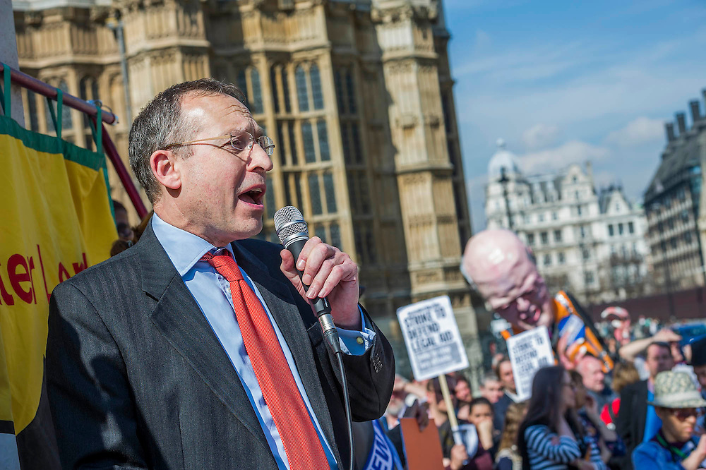 Andy Slaughter, Shadow Minister of Justice, addresses the crowd. A rally and march organised by NAPO against the governments proposed cuts to legal aid and the justice system in general.  They target Chris Grayling, the Justice Minister, by marching from Parliament to the Ministry of Justice to deliver a birthday card and cake for his birthday. Westminster, London, UK, 01 April 2014.  Guy Bell, 07771 786236, guy@gbphotos.com