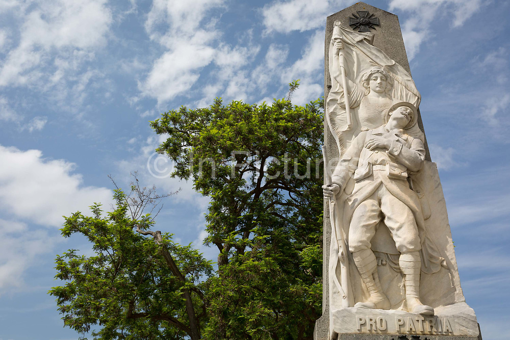 The WW1 war memorial with the Latin Pro Patria inscription on the main Le Promenade street, on 22nd May, 2017, in Lagrasse, Languedoc-Rousillon, south of France. Pro Patria is a line from the Roman lyrical poet Horaces Odes, translated as: It is sweet and proper to die for the fatherland. Lagrasse is listed as one of Frances most beautiful villages and lies on the famous Route 20 wine route in the Basses-Corbieres region dating to the 13th century.