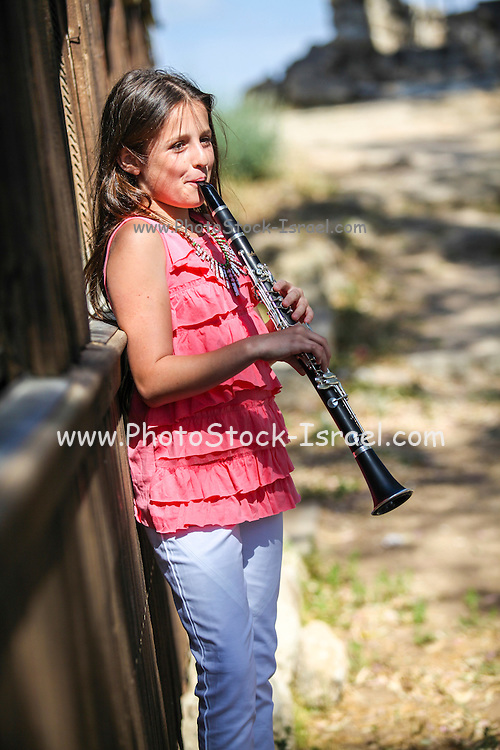Young girl of 12 plays the clarinet outdoors. Model release available