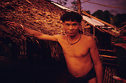 1989: Semi-nomadic Penan native, Baru at his home, a traditional Penan 'sulap' settlement made from bamboo, wood and rattan. Long Tedang, Limbang district, Sarawak, Borneo<br /> <br /> Tropical rainforest and one of the world's richest, oldest eco-systems, flora and fauna, under threat from development, logging and deforestation. Home to indigenous Dayak native tribal peoples, farming by slash and burn cultivation, fishing and hunting wild boar. Home to the Penan, traditional nomadic hunter-gatherers, of whom only one thousand survive, eating roots, and hunting wild animals with blowpipes. Animists, Christians, they still practice traditional medicine from herbs and plants. Native people have mounted protests and blockades against logging concessions, many have been arrested and imprisoned.