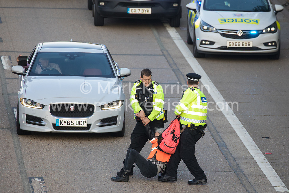 Surrey Police officers haul an Insulate Britain climate activist from the anticlockwise carriageway of the M25 between Junctions 9 and 10 where she had been protesting as part of a campaign intended to push the UK government to make significant legislative change to start lowering emissions on 21st September 2021 in Ockham, United Kingdom. Both carriageways were briefly blocked before being cleared by Surrey Police. The activists are demanding that the government immediately promises both to fully fund and ensure the insulation of all social housing in Britain by 2025 and to produce within four months a legally binding national plan to fully fund and ensure the full low-energy and low-carbon whole-house retrofit, with no externalised costs, of all homes in Britain by 2030.