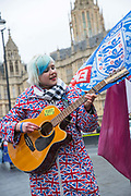 A young woman wearing a Union Jack raincoat plays an acoustic guitar outside the Houses of Parliament the day after Theresa Mays crushing defeat over her Brexit deal on the 16th January 2019 in London in the United Kingdom.