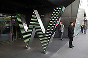 People passing the entrance to the W Hotel in central London, England, United Kingdom. This hotel chain provides an exclusive chic and boutique experience for their customers.